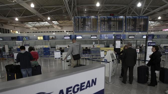Commuters stand in front of electronic check-in machines of Aegean airlines inside Athens' Eleftherios Venizelos airport