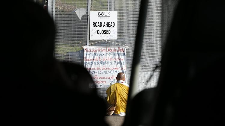 Anti-nuclear campaigner and Japanese Buddhist Monk Toyoshige Sekiguchi sits with his banner in front of a security gate outside on the G-8 summit at the Lough Erne golf resort in Enniskillen, Northern Ireland on Tuesday, June 18, 2013. The final day of the G-8 summit of wealthy nations is ending with discussions on globe-trotting corporate tax dodgers, a lunch with leaders from Africa, and suspense over whether Russia and Western leaders can avoid diplomatic fireworks over their deadlock on Syria's civil war. (AP Photo/Lefteris Pitarakis)