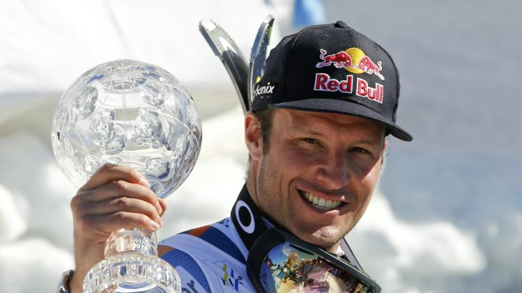Svindal of Norway celebrates with a trophy for the men's overall downhill in the FIS Alpine Skiing World Cup finals in the Swiss ski resort of Lenzerheide