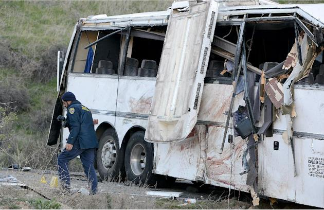 Authorities work Monday Feb. 4, 2013, at the scene of Sunday's fatal tour bus crash on Highway 38 north of Yucaipa, Calif., that left at least eight people dead and dozens injured. The cause of the Su