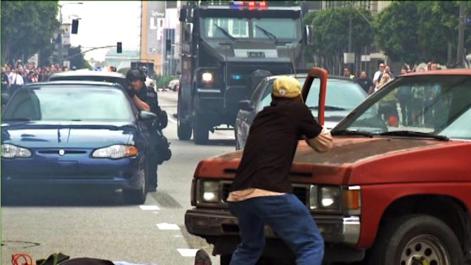 FILE - In this July 6, 2013 file still frame from a video produced by the Los Angeles Police Department, Los Angeles police take part in a downtown counterterrorism drill. A Lenco Bearcat, an armored vehicle purchased by the LAPD from a Massachusetts firm that builds them for a variety of military and police uses, stands at the rear. A Pentagon program that distributes military surplus gear to local law enforcement agencies permits even those departments that the Justice Department has censured for civil rights violations to apply for and receive lethal weaponry. That lack of communication between two parts of the federal government adds to questions about a program already facing an Obama administration review in the aftermath of the militarized police response to protesters in Ferguson, Mo.  (AP Photo/Los Angeles Police Department, File)