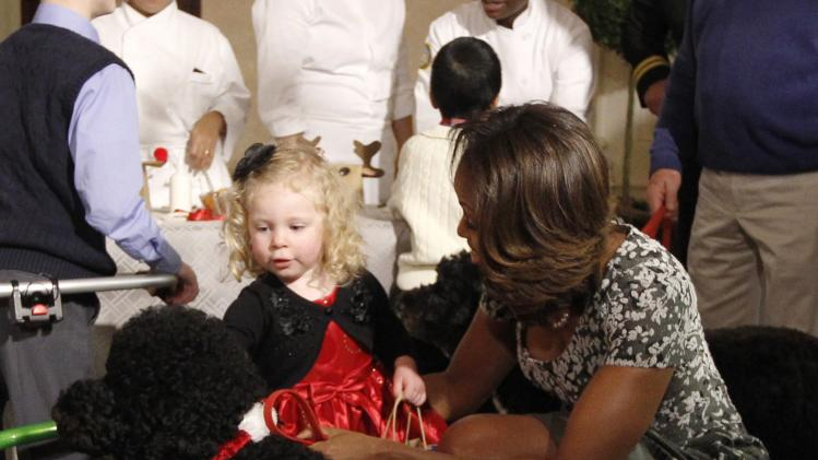 U.S. first lady Michelle Obama helps two year old Ashtyn Gardner from Mobile, Alabama, to her feet after falling at the White House in Washington