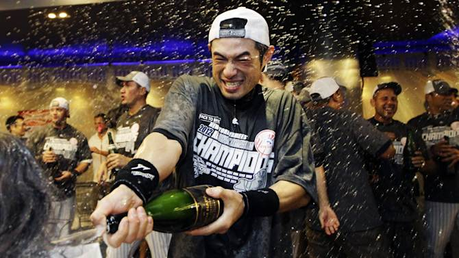 New York Yankees' Ichiro Suzuki douses the team photographer as teammates celebrate in the clubhouse after their 14-2 win over the Boston Red Sox in a baseball game and clinched the American League East title at Yankee Stadium in New York, Wednesday, Oct. 3, 2012. (AP Photo/Kathy Willens)