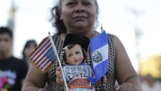 A Catholic faithful holds a figurine of baby Jesus during a religious procession on Holy Innocents Day in Antiguo Cuscatlan
