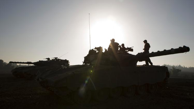 Israeli soldiers sit atop a tank near the border with Gaza