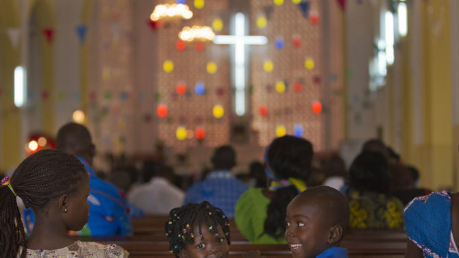 Two children sitting on a church pew look back as a New Year's Day morning mass is conducted at the Notre Dame Cathedral of the Immaculate Conception in Bangui, Central African Republic, Tuesday, Jan. 1, 2013. President Francois Bozize's government is coming under growing threat as rebels vowing to overthrow him rejected appeals from the African Union to hold their advance and try to form a coalition government. (AP Photo/Ben Curtis)