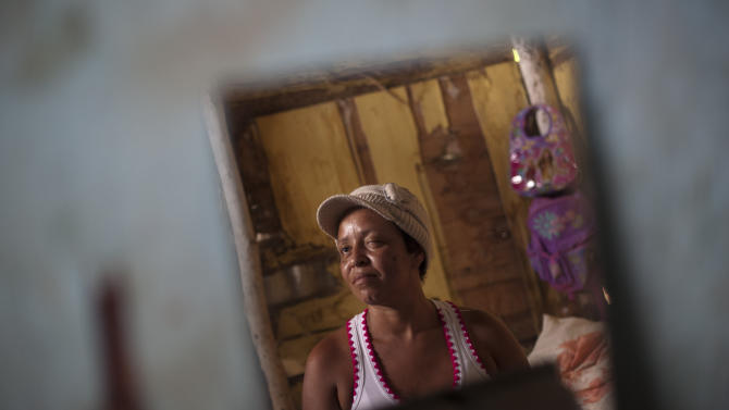 In this Oct. 28, 2013 photo, Evelina Gonzalez is reflected in a mirror in her bedroom in Maracay,Venezuela. Gonzalez is on a list of 31 breast cancer patients waiting to have tumors removed at one of the country's biggest medical facilities, Maracay's Central Hospital. The hospital's physicians sent some 300 patients in need of cancer operations home last month. Supply shortages, unsanitary conditions and equipment failures have forced them to scratch all but emergency surgeries. (AP Photo/Ariana Cubillos)
