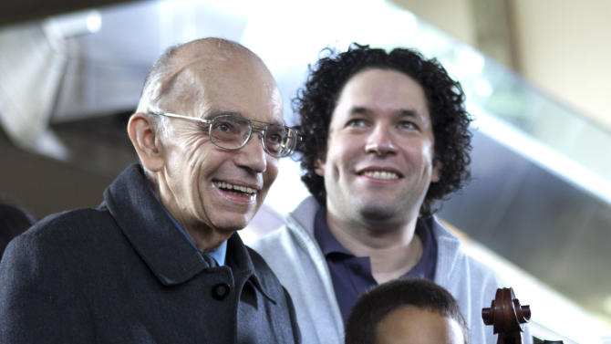 In this Thursday Feb. 16, 2012 photo, Jose Antonio Abreu, founder of the National System of Youth and Children's Orchestras of Venezuela, known as El Sistema, left, stands with Venezuela's star conductor Gustavo Dudamel, right, and a young member of the Simon Bolivar Youth Symphonic Orchestra during an event at Teresa Carreno theater in Caracas, Venezuela.  Abreu has revolutionized music education through El Sistema that has become a model worldwide and has produced talents such as Dudamel. (AP Photo/Ariana Cubillos)