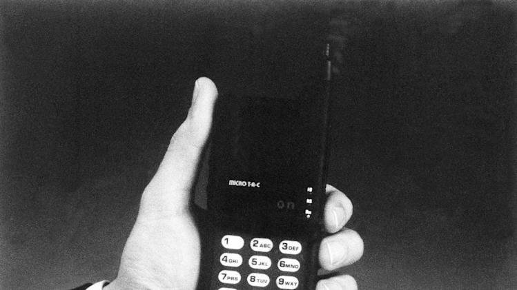 FILE- In this Tuesday, April 25, 1989, file photo, the new Motorola Micro TAC personal telephone, is unveiled during a news conference in Washington. From textile machines to the horseless carriage to email, technology has upended industries and wiped out jobs for centuries. It also has created millions of jobs, though usually not for the people who lost them. (AP Photo/Motorola)