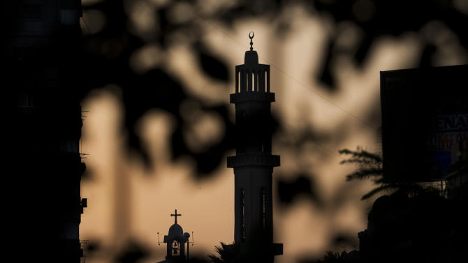 In this Wednesday, Nov. 7, 2012 picture, the minaret of a mosque and a church are silhouetted during sundown in Cairo, Egypt. Egypt's Christian minority, about 10 percent of the population of more than 80 million, has long complained of discrimination. But Christians fear things are reaching a crisis point since the ouster of President Hosni Mubarak nearly two years ago and the subsequent rise to power of Islamists. The Church itself is undergoing a major transition: A new pope, Tawadros II, is to be enthroned in Cairo on Sunday, succeeding Shenouda III, the man who led the Church for 40 years and was revered by Copts as their protector until his death in March. (AP Photo/Bernat Armangue)