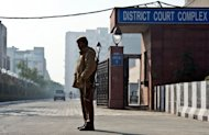 An Indian police officer stands guard outside the Saket district courthouse in New Delhi on January 21, 2013