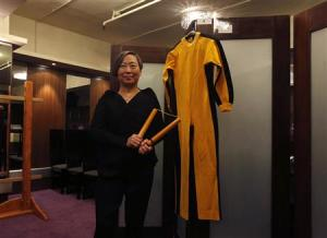 Auction house Spink vice chairman Lee poses with nunchaku and jumpsuit used by Bruce Lee during news conference in Hong Kong