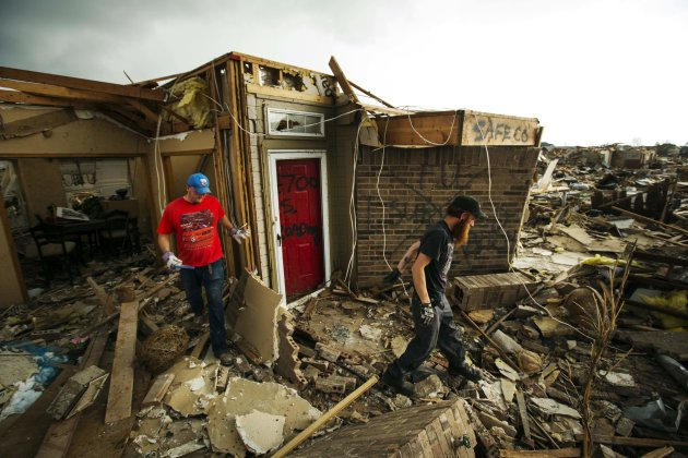 Deitz Campbell and Sean Freeland walk away from a friend's house after helping look for items to salvage after the building was destroyed by a tornado in Moore, Oklahoma