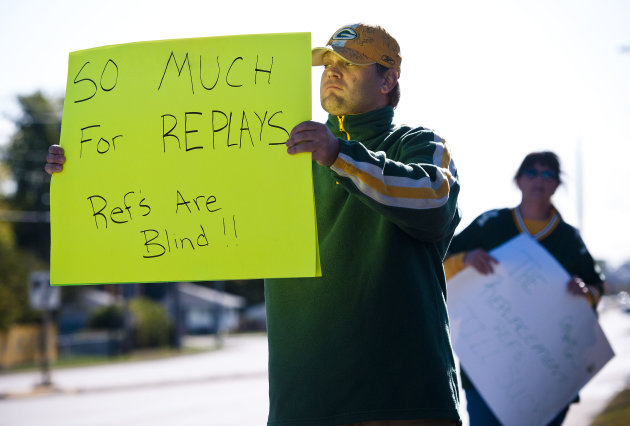 Green Bay Packers fan Mike LePak holds a sign Tuesday, Sept. 25, 2012 on Lombardi Avenue in Green Bay, Wisc., in protest of a controversial call in the Packers 14-12 loss to the Seattle Seahawks, Monday night in Seattle. Just when it seemed that NFL coaches, players and fans couldn't get any angrier, along came a fiasco that trumped any of the complaints from the weekend. (AP Photo/The Green Bay Press-Gazette, Lukas Keapproth ) NO SALES