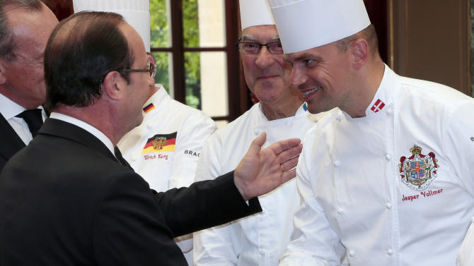 """French President Francois Hollande, left, shakes hands with Jesper Vollmer, right, Chef for the Queen of Denmark, as Bernard Vaussion, center, chef at the Paris Elysee presidential palace looks on during a reception at the Elysee palace in Paris, Tuesday July 24, 2012, following the """"Chef des Chefs Club"""" (CCC) international meeting. (AP Photo/Jacques Demarthon, Pool)"""