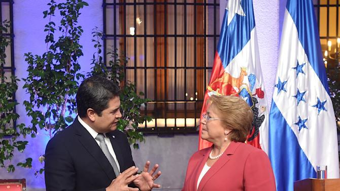Honduras' President Juan Orlando Hernandez talks to Chile's President Michelle Bachelet after a signing ceremony at the government palace in Santiago