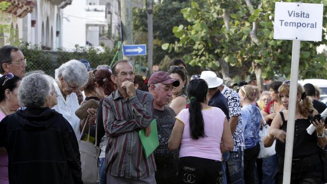 In this Jan. 7, 2013 photo, people wait to enter the U.S. Interests Section to apply for U.S. visas in Havana, Cuba. People are awaiting a new law taking effect Monday, Jan. 14, 2013 that will let the vast majority of Cubans travel abroad without having to ask for permission first or pay for costly exit visas. (AP Photo/Franklin Reyes)
