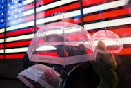 Pedestrians huddle under their umbrellas in Times Square, Monday, Oct. 29, 2012, in New York. Hurricane Sandy continued on its path Monday, as the storm forced the shutdown of mass transit, schools and financial markets, sending coastal residents fleeing, and threatening a dangerous mix of high winds and soaking rain. (AP Photo/ John Minchillo)