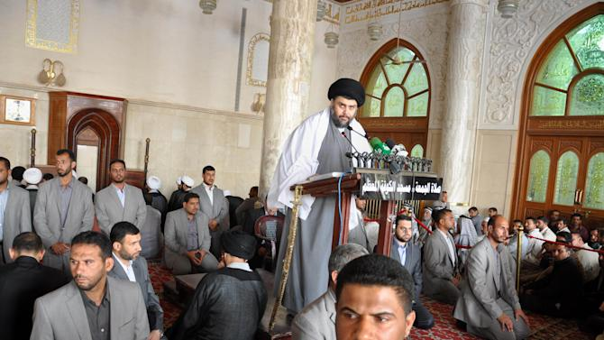 FILE - In this Friday, May 13, 2011 file photo, radical Shiite cleric Muqtada al-Sadr is surrounded by bodyguards as he speaks at Friday prayers in Kufa, 160 kilometers (100 miles) south of Baghdad, in Iraq.  Al-Sadr said in a statement made on his website Sunday, Aug. 7, 2011, that U.S. forces who stay past the Dec. 31 withdrawal deadline are fair game to attack. (AP Photo/Alaa al-Marjani, File)
