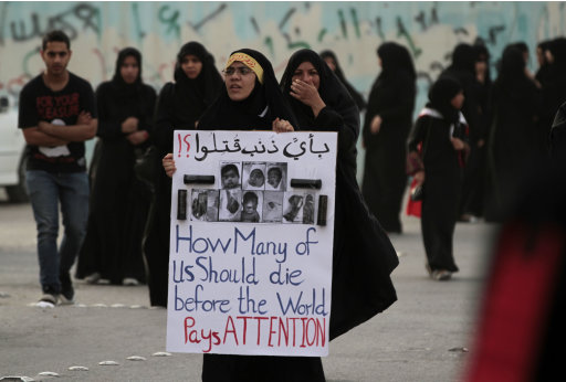 "Bahraini anti-government protesters demonstrate Thursday, June 21, 2012, in Diraz, Bahrain. Riot police used tear gas and stun grenades to disperse the demonstration against alleged deaths of infants and miscarriages blamed on excessive tear gas. Arabic on the sign reads: ""For what crime have they been killed?!"" (AP Photo/Hasan Jamali)"