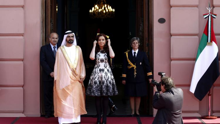 Argentina's President Fernandez de Kirchner arranges her hair as she poses next to Sheikh Mohammed Bin Rashid Al Maktoum, Vice President and Prime Minister of the United Arab Emirates, in Buenos Aires