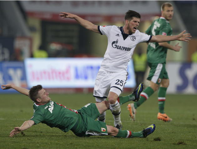 Schalke's Klaas-Jan Huntelaar of the Netherlands, right, and Augsburg's Daniel Baier challenge for the ball during the German first division Bundesliga soccer match between FC Augsburg and FC