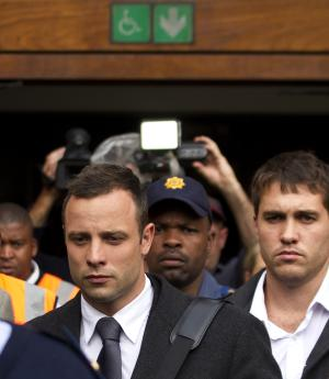 Oscar Pistorius, left, with unidentified man leaves the high court in Pretoria, South Africa, Tuesday, March 11, 2014. Pistorius is charged with murder for the shooting death of his girlfriend, Reeva Steenkamp, on Valentines Day in 2013. (AP Photo/Themba Hadebe)