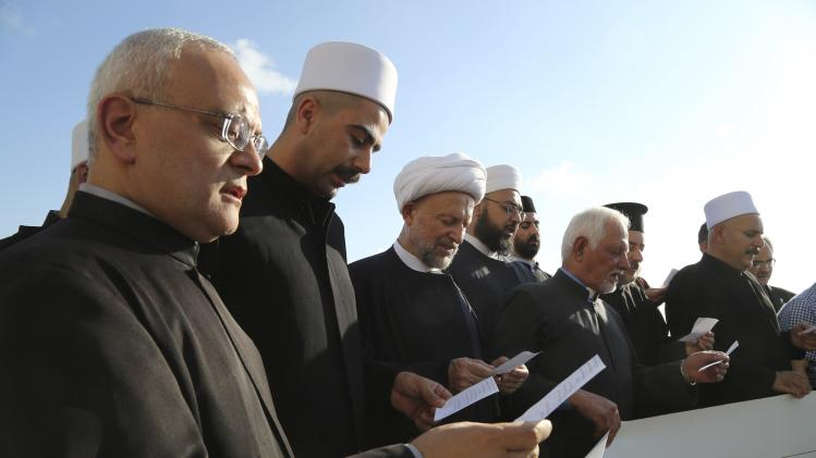 Lebanese Shi'ite and Sunni Muslim Sheikhs, along with Christians and Druze clerics, pray during a sit-in to express solidarity with the Christians of Mosul and against Israel's military action in Gaza, in Beirut