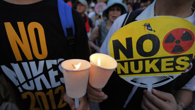 Protesters holding candle during the anti-nuclear rally outside the parliament house in Tokyo, Sunday, July 29, 2012. Thousands of the protesters rallied to demand the government abandon nuclear power after the accident last year in northern Fukushima. (AP Photo/Itsuo Inouye)