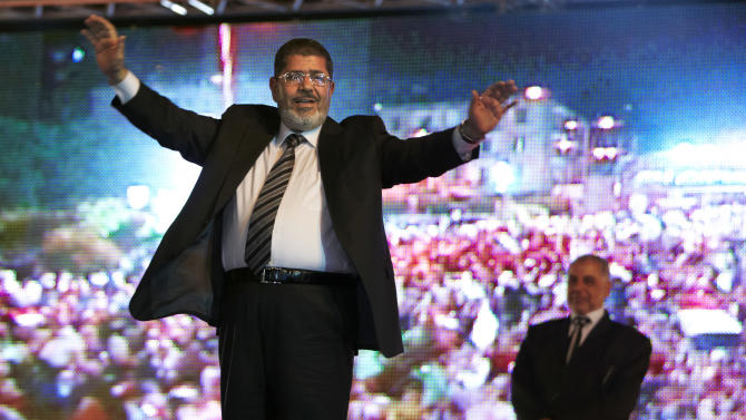 "FILE - In this Sunday, May 20, 2012 file photo, the Muslim Brotherhood's presidential candidate Mohammed Morsi hold a rally in Cairo, Egypt. A statement on the Egyptian president's office's Twitter account has quoted Mohammed Morsi as calling military measures ""a full coup."" The denouncement was posted shortly after the Egyptian military announced it was ousting Morsi, who was Egypt's first freely elected leader but drew ire with his Islamist leanings. The military says it has replaced him with the chief justice of the Supreme constitutional Court, called for early presidential election and suspended the Islamist-backed constitution.(AP Photo/Fredrik Persson, File)"