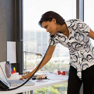 Businesswoman-on-phone-while-using-laptop_web