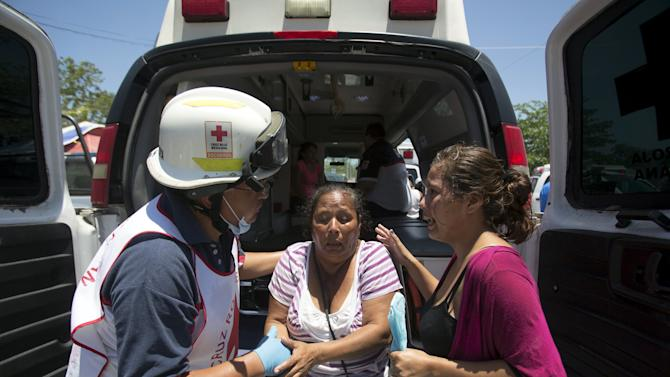 A Red Cross paramedic attends to a woman experiencing shock outside the jail during a clash of rival groups in the prison of Cancun