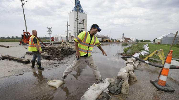 New Hartford Fire Department Chief Brad Schipper steps over sandbags after checking a pump, Tuesday, June 25, 2013, in New Hartford, Iowa. Hundreds of residents obeyed an order to evacuate their homes in this northeast Iowa town Tuesday before floodwaters from a rising creek could strand them. (AP Photo/Charlie Neibergall)