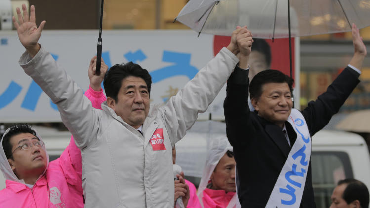 FILE -In this Dec. 15, 2012 file photo, Japan's main opposition Liberal Democratic Party (LDP) President Shinzo Abe, left, and then candidate of the party Yoshitaka Shindo acknowledge crowd during a campaign rally for the Dec. 16 parliamentary elections in Kawaguchi, near Tokyo. Internal Minister Yoshitaka Shindo on Saturday, April 12, 2014 visited a Tokyo war shrine that honors executed war criminals among others in a move that could reignite tensions with Japan's neighbors ahead of President Barack Obama's Asian tour. (AP Photo/Itsuo Inouye, File)