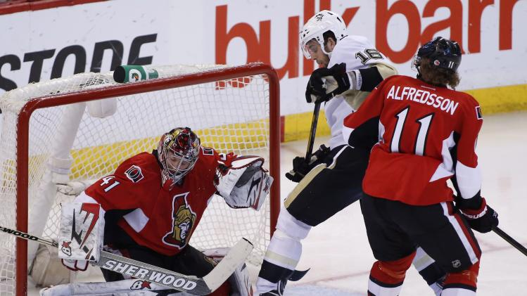 Ottawa Senators goaltender Craig Anderson, left, makes a save while Pittsburgh Penguins Brandon Sutter and Senators Daniel Alfredsson jostle in front of the net during the first overtime period of game four of their Stanley Cup Eastern Conference semi-final NHL hockey game at Scotiabank Place in Ottawa on Sunday, May 19, 2013.  (AP Photo/The Canadian Press, Patrick Doyle)