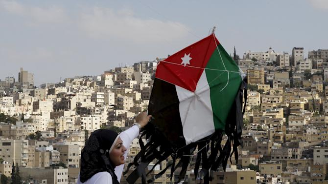 Woman prepares to fly a kite of a Jordanian national flag during an event to celebrate Jordan's Independence Day at the Amman Citadel