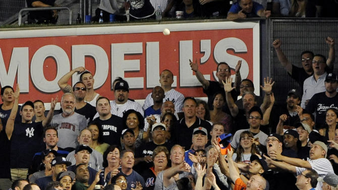 New York Mets center fielder Kirk Nieuwenhuis (9) watches fans try to catch a two-run home run by New York Yankees' Mark Teixeira in the sixth inning of an interleague baseball game on Saturday, June 9, 2012, at Yankee Stadium in New York. (AP Photo/Kathy Kmonicek)