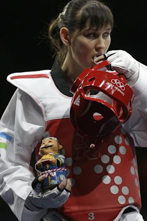 Uzbekistan's Natalya Mamatova holds a handmade doll before presenting it to France's Anne-Caroline Graffe prior to their match in women's plus 67-kg taekwondo competition at the 2012 Summer Olympics, Saturday, Aug. 11, 2012, in London. (AP Photo/Ng Han Guan)