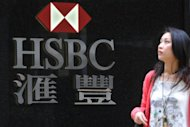 A woman passes by an HSBC in Hong Kong. The bank, Europe's biggest, said on Tuesday that group net profits hit $2.58 billion (1.98 billion euros) in the first quarter, down 38 percent on changes to debt valuation, while pre-tax earnings soared