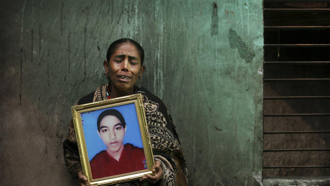 In this Friday, Dec. 21, 2012 photo, Bangladeshi Rokeya Begum displays a photograph of her 18-year-old daughter Henna Akhtar, a sewing machine helper who died in the fire at Tazreen Fashions, in the garment district in Ashulia, near Dhaka, Bangladesh. When fire ravaged the Bangladeshi garment factory, killing 112 workers, dozens of their families did not even have a body to bury because their loved ones' remains were burned beyond recognition. Two months later, they have yet to receive any of the compensation they were promised - not even their relatives' last paychecks.  (AP Photo/Kevin Frayer)
