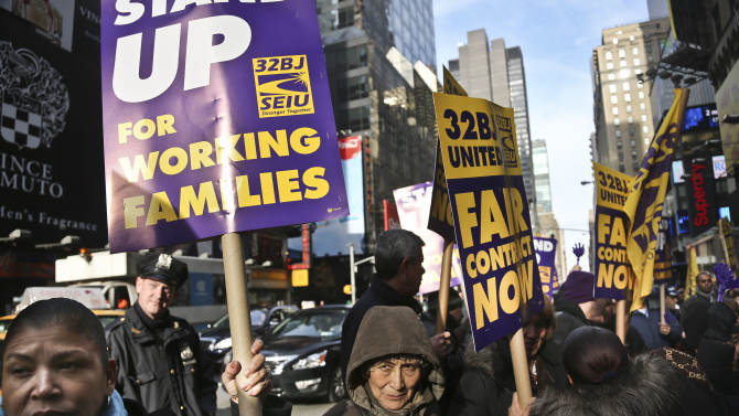 FILE - In this Wednesday, Dec. 12, 2012 file photo, cleaners, porters and matrons of theater union SEIU Local 32BJ demonstrate outside the Broadway League's office, before a vote authorizing a strike in New York. The union representing hundreds of Broadway theater cleaners, porters, elevator operators and bathroom attendants has reached a tentative labor agreement with the Broadway League to avert a strike. The potential deal, announced Monday, Dec. 17, 2012, must be ratified by the 250 theater workers represented by 32BJ, a process expected soon. (AP Photo/Bebeto Matthews, File)