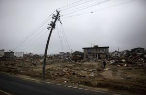 File photo of a man walking near a damaged power pole in Watari