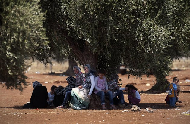 FILE - In this Wednesday, Aug. 15, 2012 file photo, a displaced Syrian family sits under a tree by the border with Turkey after they left their home, in the town of Azaz on the outskirts of Aleppo, Sy