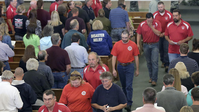 Members of the West Volunteer Fire Department leave the church after attending a service at St. Mary's Church of the Assumption, Friday, April 19, 2013, two days after an explosion at a fertilizer plant in West, Texas. The massive explosion at the West Fertilizer Co. Wednesday night killed 14 people including numerous members of the West Volunteer Fire Department and injured more than 160. (AP Photo/Charlie Riedel)