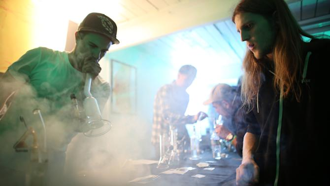 "FILE - In this April 20, 2013 file photo, Nick Villejo of Refine collective and Jared Smith smoke vaporized marijuana during ""Studio 4/20,"" a legal marijuana celebration put on by DOPE Magazine, at 7 Point Studios in Seattle. The event billed itself as the largest local marijuana celebration since pot was legalized by Washington state voters. After months of intensive research, public meetings and public reaction, state officials on plan to release their draft rules governing Washington's new legal marijuana industry on Thursday, May 16, 2013. (AP Photo/seattlepi.com, Joshua Trujillo, File) MAGS OUT; NO SALES; SEATTLE TIMES OUT; MANDATORY CREDIT; TV OUT"
