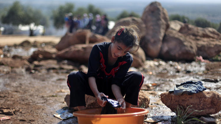 A Syrian girl who fled with her family from the violence in their village, washes clothes at a displaced camp, in the Syrian village of Atma, near the Turkish border with Syria, Monday, Nov. 5, 2012. (AP Photo/ Khalil Hamra)
