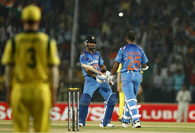 Indian players Virat Kohli and Shikhar Dhawan celebrates during the 6th ODI between India and Australia at Vidarbha Cricket Association Stadium in Nagpur on Oct.30, 2013. (Photo: IANS)