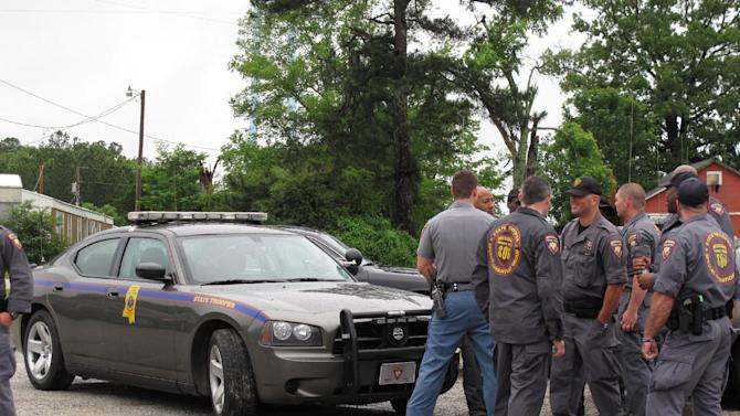 Members of the Mississippi Highway Patrol gather at a staging area during the search for a missing Tennessee family, Monday, May 7 2012 in Guntown, Miss. State troopers stopped vehicles at roadblocks Monday and officers searched the yard of a home in northern Mississippi, seeking to unravel the mysterious disappearance of a Tennessee mother and her three daughters and find the family friend accused of abducting them. (AP Photo/Adrian Sainz)