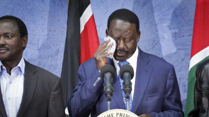 Losing presidential candidate Raila Odinga, right, wipes his brow as he speaks to the media and accepts the Supreme Court ruling upholding the election result, and urges unity amongst Kenyans, at a press conference in Nairobi, Kenya, Saturday, March 30, 2013. Kenya's Supreme Court on Saturday upheld the election of Uhuru Kenyatta as the country's next president, ending an election season that riveted the nation amid fears of a repeat of the 2007-08 postelection violence. (AP Photo/Khalil Senosi)