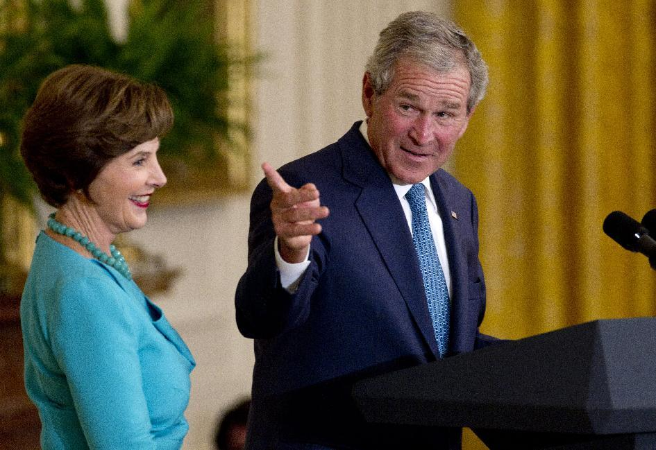 Former President George W. Bush, accompanied by former first lady Laura Bush, gestures in the East Room of the White House in Washington, Thursday, May 31, 2012, during a ceremony to unveil  their  portraits. (AP Photo/Carolyn Kaster)†